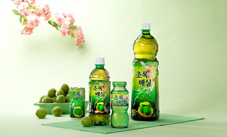 웅진식품 초록매실 브랜드를 표현하는 매화꽃과 제품 이미지입니다.
